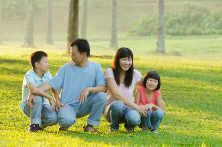 8 year old girl: Family lying outdoors being playful and smiling, Outddor portrait