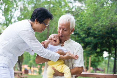 comforted: Asian crying baby comforted by grandparents at outdoor garden