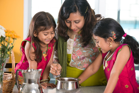 indians: indian mother cooking with her daughters at kitchen