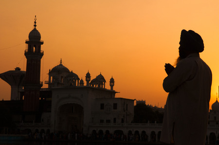 gurudwara: silhouette of pilgrim praying at the holy temple of amritsar, india