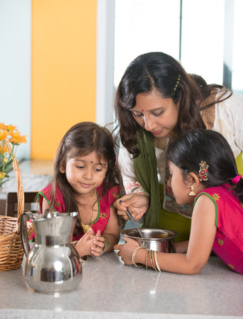 family life: indian mother cooking with her daughters at kitchen