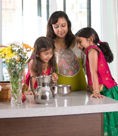 indian food: indian mother cooking with her daughters at kitchen