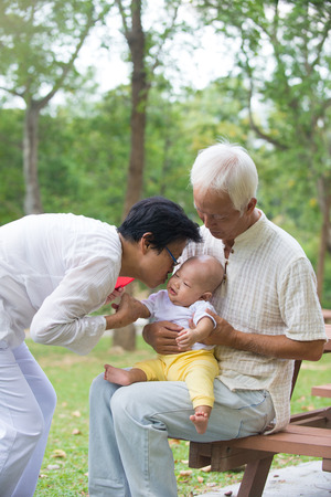 grandmother and grandson: chinese grandfather and grandmother playing with baby grandson at outdoor Stock Photo