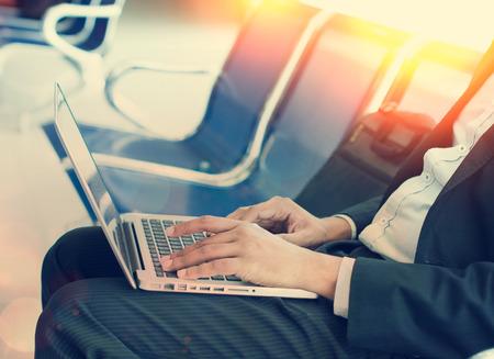 ビジネスの男性と朝空港ターミナルでのノート パソコン