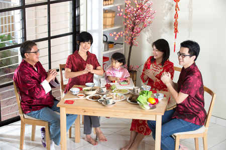 familia cenando: familia china dando saludos durante el año nuevo chino