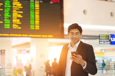 mobile business: indian male at airport terminal in the early morning
