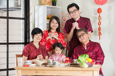 reunion dinner: chinese family giving greetings during chinese new year