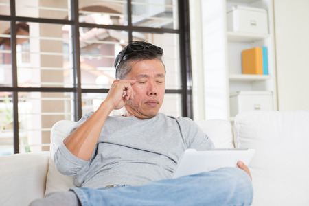 asian man with eyes problem after long hours of using computer tablet Stock Photo
