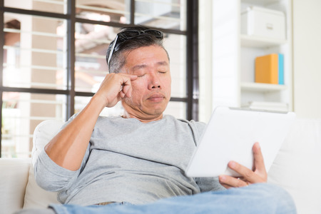 long hours: asian man with eyes problem after long hours of using computer tablet Stock Photo