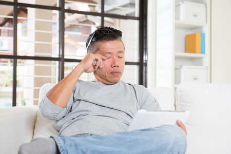 asian man with eyes problem after long hours of using computer tablet Standard-Bild