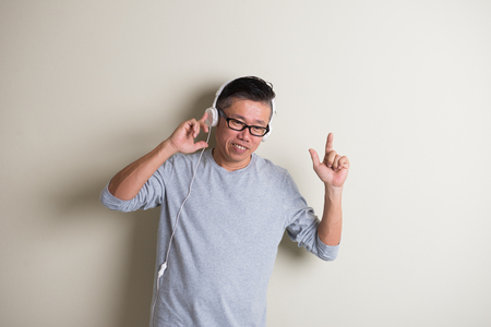 southeast asian ethnicity: asian senior listening to music