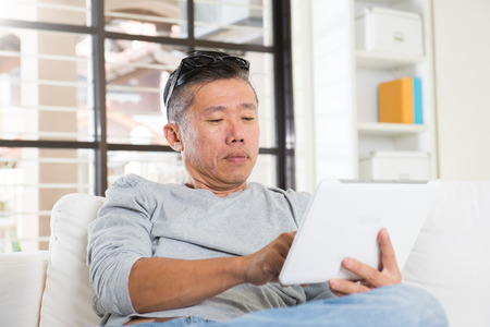 senior female: asian man with eyes problem after long hours of using computer tablet Stock Photo