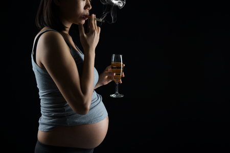 beer wine: pregnant mother smoking and drinking Stock Photo