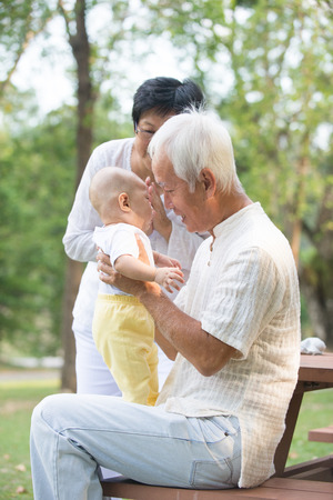 old man happy: chinese grandfather and grandmother playing with baby grandson at outdoor Stock Photo