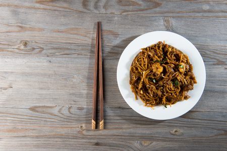 char: Fried Penang Char Kuey Teow top down view which is a popular noodle dish in Malaysia, Indonesia, Brunei and Singapore