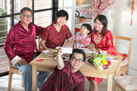 reunion dinner: Celebrating Chinese New Year, reunion dinner. Happy Asian Chinese multi generation family with red cheongsam selfie while dining at home. Stock Photo