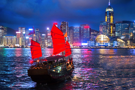 victoria harbor: hong kong night view with junk ship on foreground