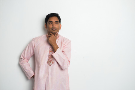kurta: traditional indian male thinking with plain background and copyspace on right