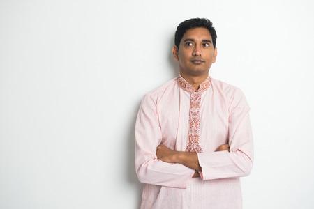caras felices: masculino indio tradicional pensamiento con el fondo plano y copyspace a la derecha