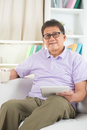 asian elderly: asian Senior Man Reading With Drink At Home