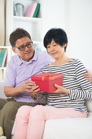 asian adult: Senior man giving Christmas present to his wife
