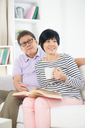 asian wife: senior asian couple reading a book together at home. Stock Photo