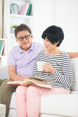 convivencia familiar: Pares asiáticos mayores que leer un libro juntos en casa.