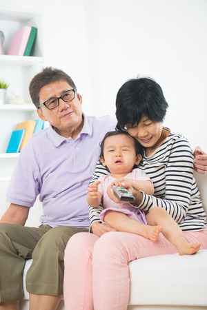 asian grand parents with crying grand daugther Imagens