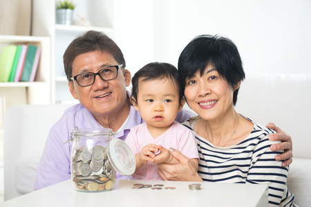 family sofa: Asian family saving money indoor, financial concept, grandparents and grandchild living lifestyle at home.