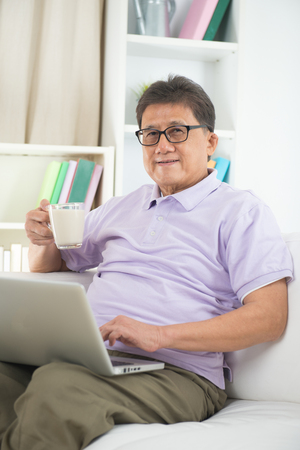 old asian: asian Senior Man Reading With Drink At Home
