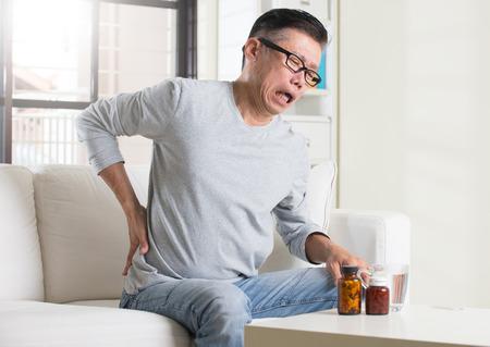 asian senior with back pain medicine