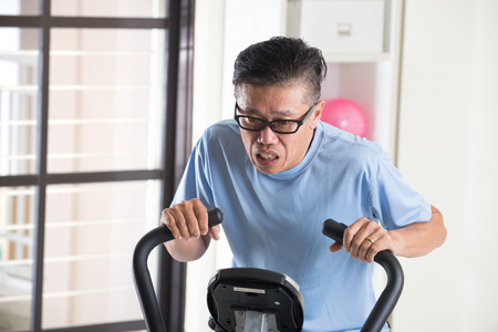 burnt out: tired asian senior male on exercise bike Stock Photo
