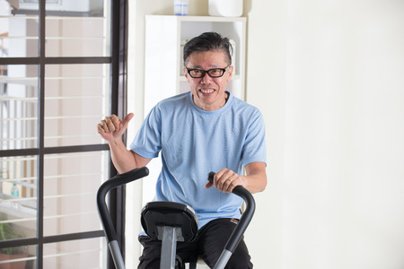thumbs: asian senior male thumbs up on exercise bike