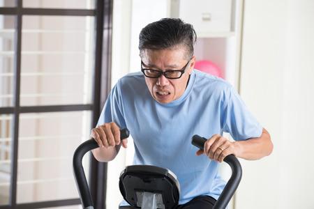 tired asian senior male on exercise bike Stock Photo