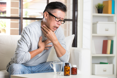 senior man on a neck pain: asian senior with throat pain and medicine