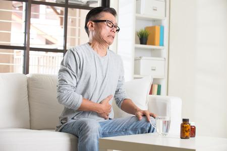 dolor de estomago: asi�tico mayor con dolor de est�mago y la medicina Foto de archivo