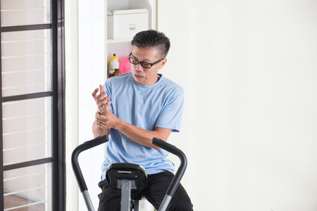 hombre viejo: senior de lesión en la mano masculino asiático en bicicleta de ejercicio