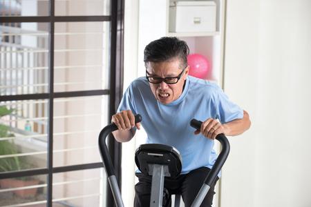 agotado: cansado senior masculino asiático en bicicleta de ejercicio