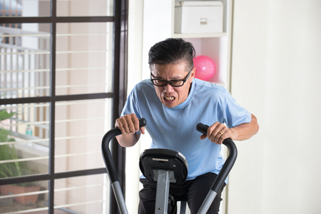 exhausted: tired asian senior male on exercise bike Stock Photo