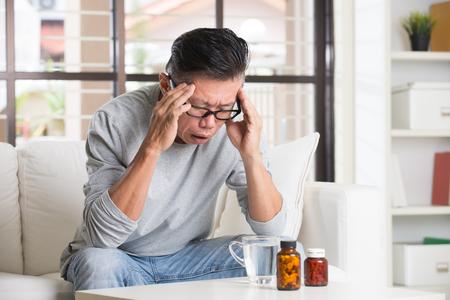 headache pain: asian senior with severe headache and medicine