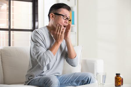 la boca: asiático mayor con dolor en la boca y la medicina Foto de archivo