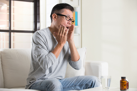 mouth pain: asian senior with mouth pain and medicine Stock Photo