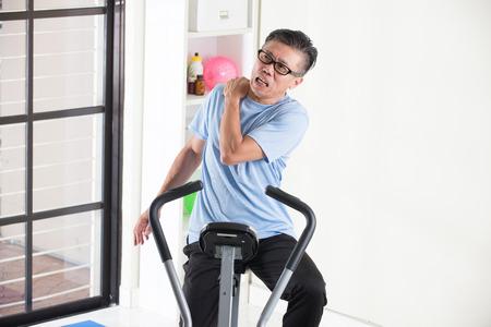 shoulder ride: asian senior male shoulder injury on exercise bike