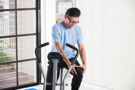 old asian: asian senior male knee pain on exercise bike Stock Photo