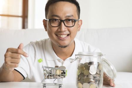 savings problems: asian male saving money Stock Photo