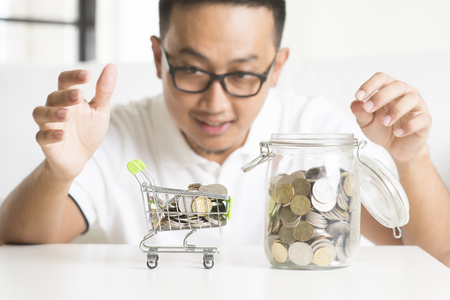 failed: asian male saving money Stock Photo