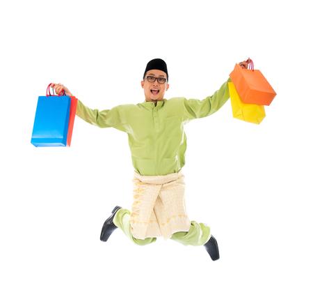 raya: Traditional Malay male shopping and jumping in joy during hari raya ramadan festival