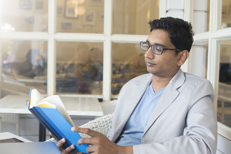 learning arabic: young indian male reading book on cafe Stock Photo