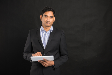 male face: indian business male using tablet in black background