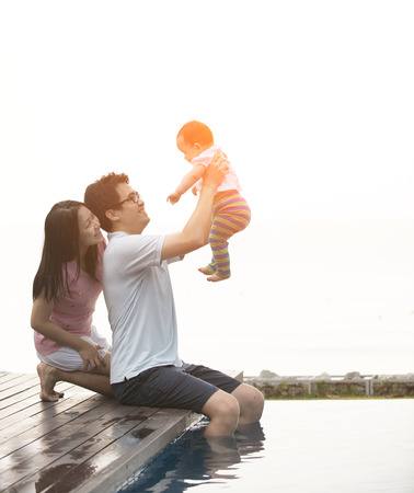 asian family having fun at the pool